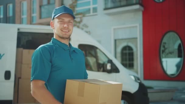 Portrait of Handsome Delivery Man Holds Cardboard Box Package Standing in Modern Stylish Business District with Delivery Van in Background. Smiling Courier On Way to Deliver Postal Parcel to Client