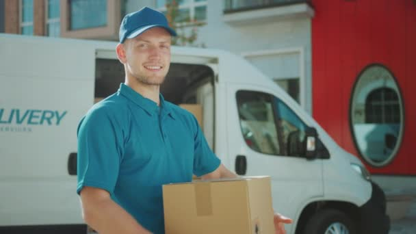 Portré Jóképű Szállító Férfi tartja karton doboz csomag Álló Modern Stílusos Üzleti kerületben Szállítási Van a háttérben. Mosolygós futár Úton, hogy kézbesítse postai csomagot ügyfelének