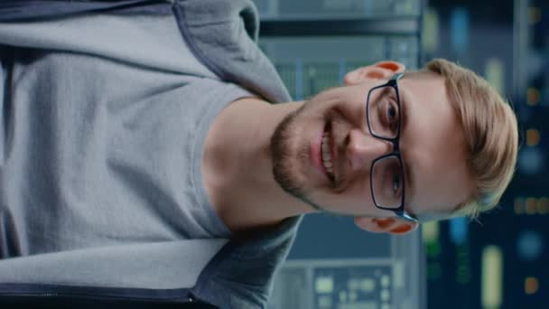 Portrait of a Smart and Handsome IT Specialist Wearing Glasses Smiles at the Camera. In the Background Personal Computers with Screens in Data Center. Vertical Screen Orientation Video 9:16