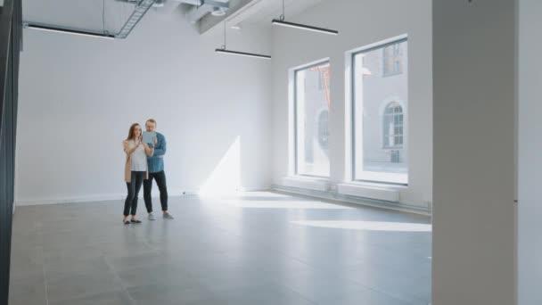 Mladý hipster muž a žena stojí v prázdné bílé kanceláři a mapovat ji s rozšířenou realitou software na tabletu. Sluneční světlo svítí velkými okny. Místnost má sledovací body pro video software.
