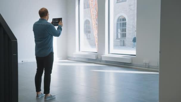 Mladý Hipster Man v brýlích stojící v prázdné kanceláři a mapovat jej s rozšířenou realitou software na tabletu. Sluneční světlo svítí velkými okny. Místnost má sledovací body pro video software.