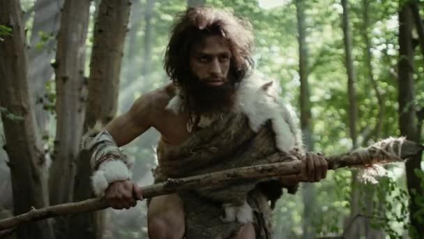 Porträt eines Höhlenmenschen mit Tierhaut und Pelz auf der Jagd mit einem steinernen Speer im Urwald. Urzeitlicher Neandertaler-Jäger bereit, Speer in den Dschungel zu werfen
