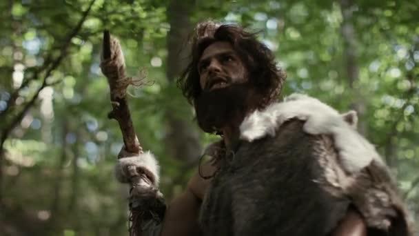 Ősi ősember visel állati bőr Holds kő hegyű lándzsa néz körül, felfedez őskori erdő vadászat az állat zsákmány. Neander-völgyi vadászat. Alacsony szögű ívre néző