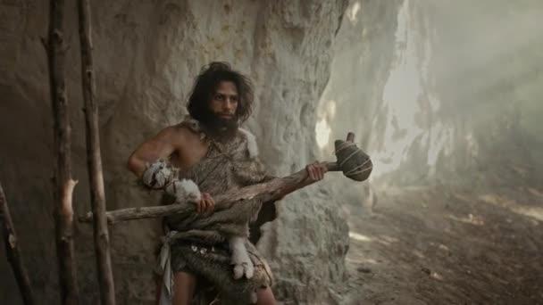 Urzeit-Höhlenmensch mit Tierhaut hält steinernen Hammer in der Hand, kommt aus der Höhle und schaut sich im Urwald um, bereit, tierische Beute zu jagen. Neandertaler auf der Jagd in den Dschungel Bogenschuss