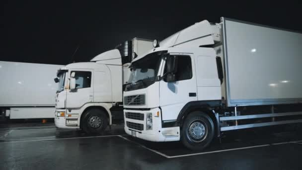 White Semi-Trucks with Cargo Trailer Drives Standing on Overnight Parking Place. Drivers Resting at Night on the Overnight Parking Lot. Arc Shot
