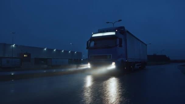 Blue Long Haul Semi-Truck mit Frachtanhänger voller Güter reist nachts auf der Freeway Road durch Regen, Nebel und Schnee quer durch den Kontinent. Bereich Industrielager. Frontalzusammenstoß