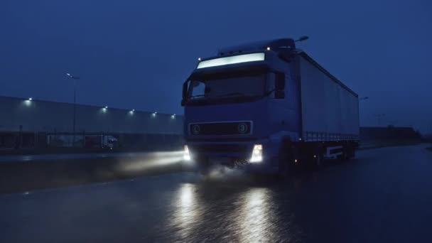 Ein blauer Langstreckenauflieger mit Güteranhänger fährt nachts über die Autobahn und überquert den Kontinent durch Regen, Nebel, Schnee. Bereich der Industrielager. Vorne nach Schuss