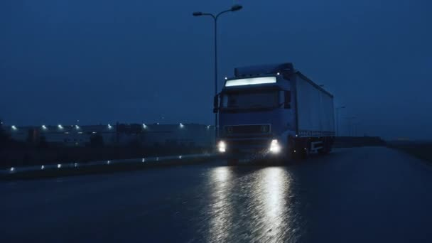 Long Haul Semi-Truck with Cargo Trailer Full of Goods Travels At Night on Freeway Road, Driving Across Continent Through Rain, Fog, Snow. Průmyslové skladiště. Přední následující pomalý pohyb výstřel