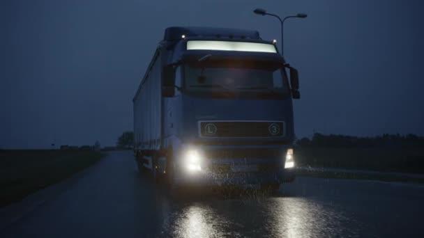 Long Haul Semi-Truck with Cargo Trailer Full of Goods Travels At Night on Freeway Road, Driving Across Continent Through Rain, Fog, Snow. Průmyslové skladiště. Přední následující pomalý pohyb výstřel