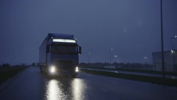 Long Semi-Truck with Cargo Trailer Full of Goods Travels on Highway Road. Driving in Morning Across Continent Through Rain, Fog, Snow. Industrial Warehouses Area. Front Following Slow Motion Shot