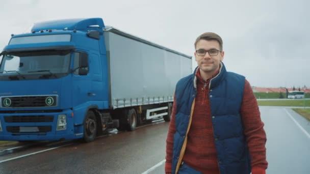Profesionální mladý řidič kamionu kříží ruce a úsměvy. Za ním zaparkoval Blue Long Haul Semi-Truck s nákladním přívěsem