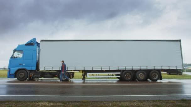 Lastwagenfahrer überquert im ländlichen Raum die Straße und steigt in seinen blauen Langstreckenauflieger mit Anhänger. Logistikunternehmen, das Waren über den Kontinent transportiert. Seitenansicht Kamerafahrt