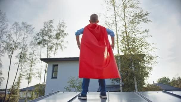 A fiú egy szuperhős szerepét játssza. Egy ház tetején áll, kezével a derekán. A fiatalember fényes vörös köpenyt visel. A Napot nézi..
