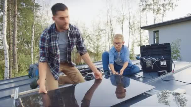 Otec a syn instalují solární panely na kovový základ s vrtačkou. Pracují na střeše domu za slunečného dne a na plácnutí. Koncept ekologické obnovitelné energie v domácím a kvalitním rodinném čase.