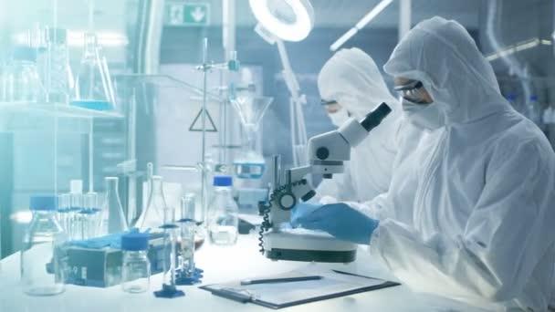 Egy biztonságos, magas szintű laboratóriumi tudósok egy overall kutatók egy kutatási. Beállítja egy Petri-csészébe harapófogó minták és akkor megvizsgálja azokat mikroszkóp alatt, és kollégája írja le eredmények