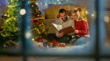 View Through the Window. Beautiful Lovely Couple is Sitting Under Christmas Three with Gifts and Reading a Book.