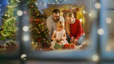 Looking Through Snowy Window. Happy Father, Mother and Daughter Sitting Under Christmas Tree. Daughter Opens Her Presents.