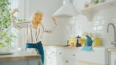 Authentic Senior Female in Blue Jeans and White Striped Blouse is Creatively Dancing in the Kitchen. Sunny Modern Kitchen with Healthy Lifestyle Vibes. Happy Beautiful Pensioner Relaxing at Home.