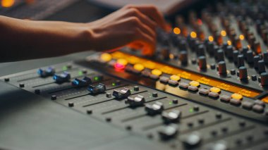 Modern Music Record Studio Control Desk with Automatic Equalizer, Mixer and other Professional Equipment. Switchers, Buttons, Faders, Sliders, Motorized Faders Move, Record, Play Hit Song. Close-up