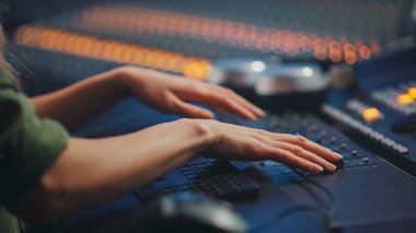 Audio Engineer, Musician, Artist Works in the Music Record Studio, Control Desk Mixer. Female Hands Moving Faders, Switchers, Buttons, Faders, Sliders to Broadcast, Record, Play Hit Song. Close-up