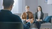 Nesoustředěný pár na poradenské sezení s psychoterapeutem. Zaměření na zadní části terapeuta dělat si poznámky a mluvit: Lidé sedí na analytik gauč, Diskuse o psychologických a vztahových problémech