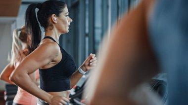 Beautiful Athletic Sports Woman Wearing Wireless Headphones, Listens to a Podcast or Sport Music Playlist while Running on a Treadmill. In Background Fit Athletes Training in the Gym