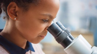 Portrait of Smart Little Schoolgirl Looking Under the Microscope. In Elementary School Classroom Cute Girl Uses Microscope. STEM science, technology, engineering and mathematics Education Program