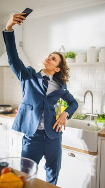 Happy Young Man with Long Hair Making a Selfie on His Smartphone in a Kitchen while Wearing Blue Business Suit. He is Standing Like a Super Model. Vertical Shot in a Cozy Apartment.