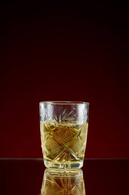 Glass with alcohol in a transparent glass with ice and mint on a red background