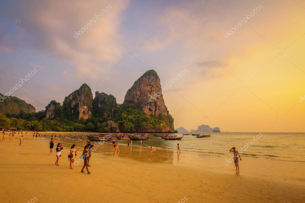 Tourists rest at the Railay Beach before sunset