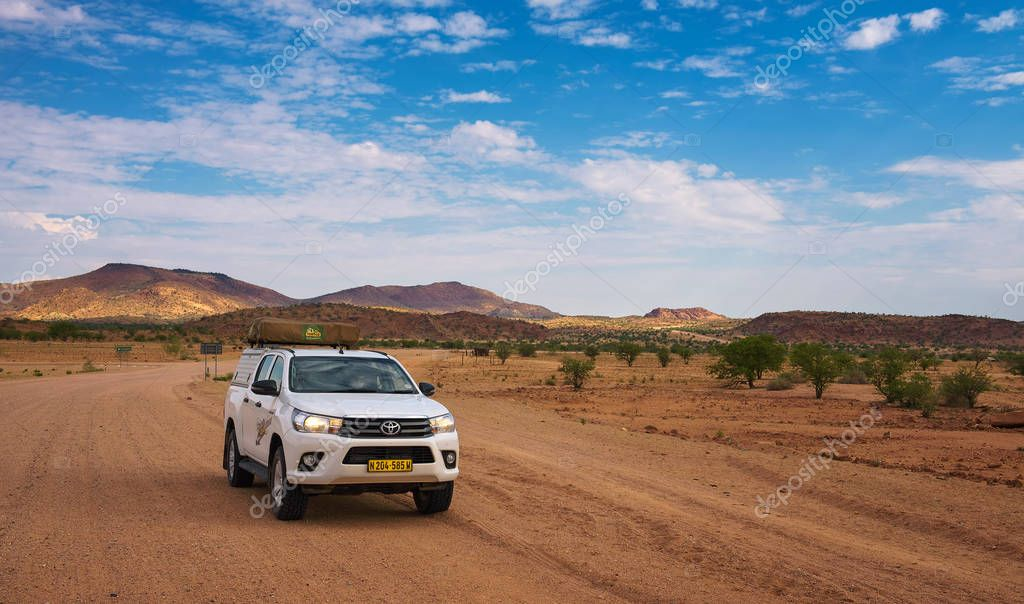 4x4 rental car equipped with a roof tent driving through Damaraland in Namibia