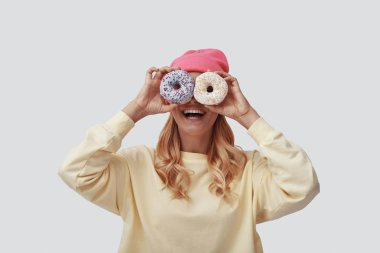 Attractive young woman covering eyes with donuts and smiling while standing against grey background