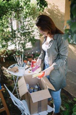 "Картина, постер, плакат, фотообои ""женщина-художник держит краски трубки над коробкой с аксессуарами для краски"", артикул 394360044"