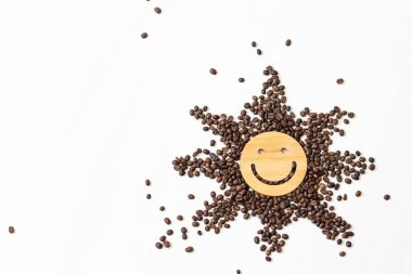 Coffee is a healthy, mood-enhancing drink. Star or sun from roasted coffee beans with a smile in the middle on a white background