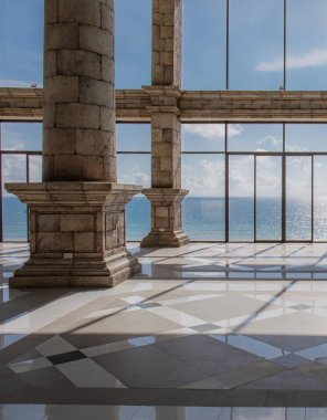Empty lounge area with marble floorand view of a ocean and sky.