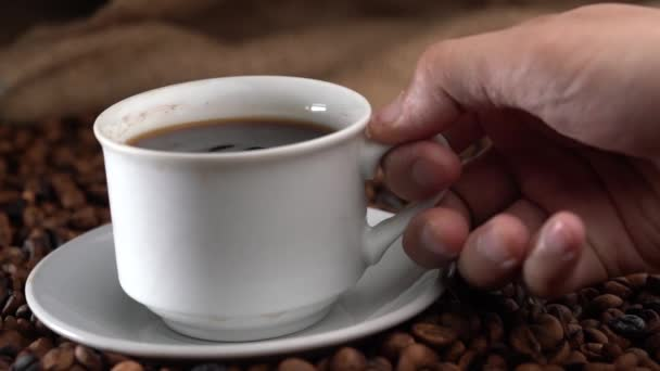 hands lifting up cup of coffee from saucer