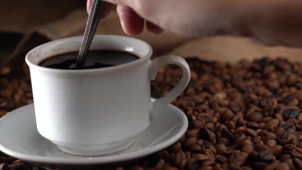 Hand Stirring Coffee In White Cup With Spoon
