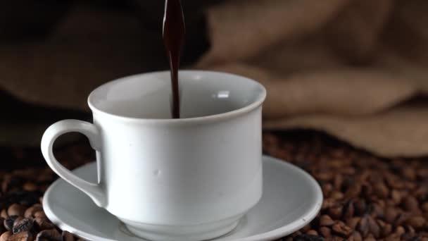 Öntés egy csésze forró kávét és pörkölt kávébab az asztalra, lassított
