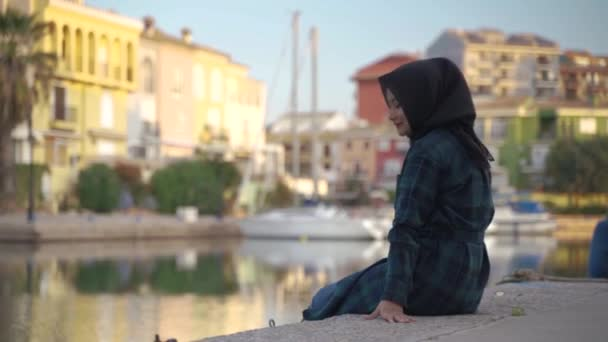 young muslim Asian women wearing black scarf or hijab sitting and relax enjoying the view of colorful house by the river