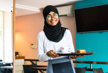 Male, Maldives - February 11th, 2019: Portrait of a muslim woman wearing hijab and eyeglasses who works as waitress in a coffee store in Male, Maldives.