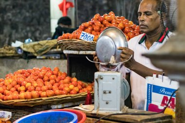 Port Louis, Mauritius - January 29, 2019: A vegetables vendor putting tomatoes inside a bag for a customer at the Central Market in Port Louis, Mauritius.