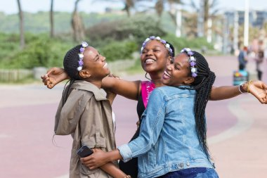 Durban, South Africa - January 07th, 2019: Three beautiful black young women laughing and celebrating a birthday outdoors in Durban, South Africa.