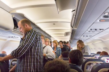 Passengers standing to disembark from an airplane.