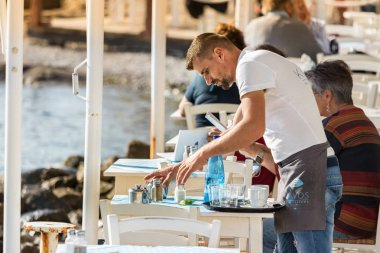 A male waiter clearing a table outdoors at a greek tavern.