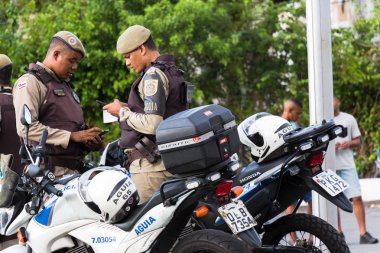 Salvador Bahia, Brazil - February 11th, 2018: it is Carnival time in Salvador and the Motorcycle Police are on the street at the waterfront looking their mobiles phones at Elevator Lacerda area.