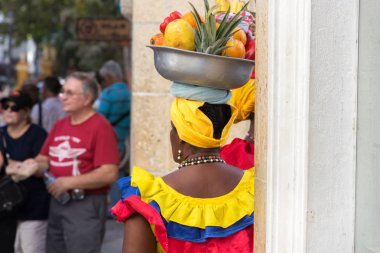 Rear view of a palenquera selling fruits in Cartagena.