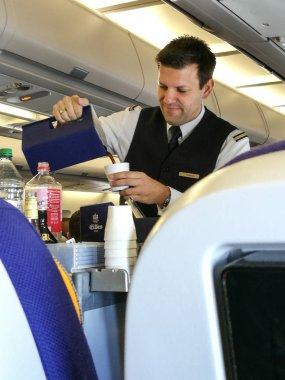 A male flight attendant serving in the economy class.