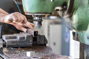 A male worker operating a milling cutter drill machine.