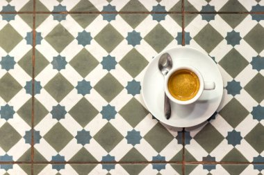 Cup coffee espresso over a diamond shape pattern background.