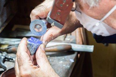Jeweler engraving diamonds on a ring.